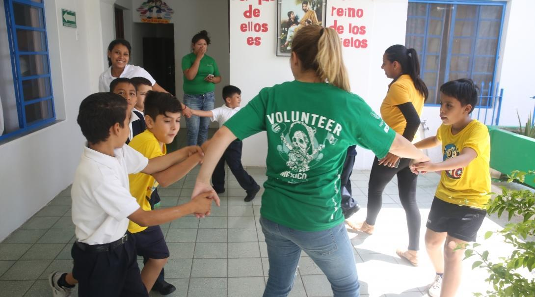 A student studying Spanish in Mexico volunteers in a local school with young children and plays educational games.